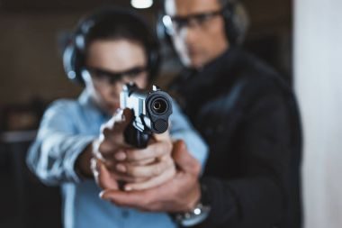 Instructor helping customer in shooting gallery with gun on foreground