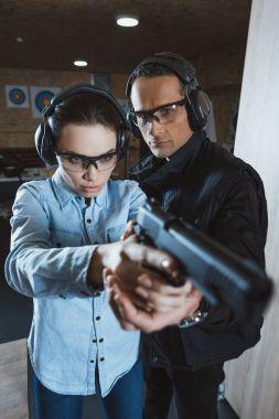 instructor helping customer holding gun
