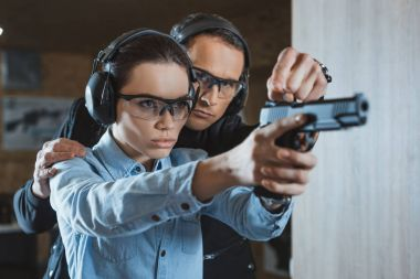 instructor helping customer in shooting gallery