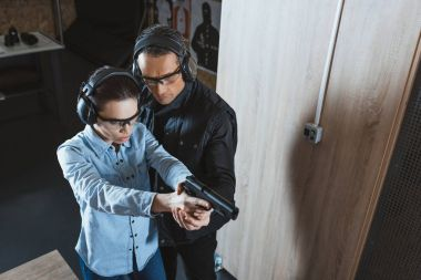 overhead view of instructor helping customer in shooting gallery