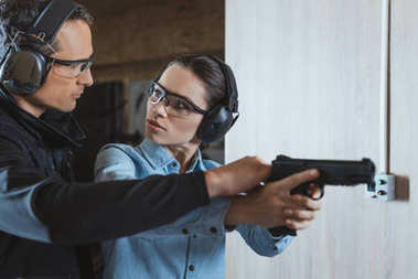 male instructor helping customer in shooting range