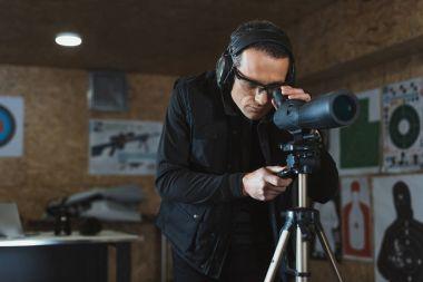 Man looking through binoculars at remote target in shooting range stock vector