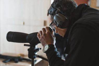 man looking through binoculars in shooting range