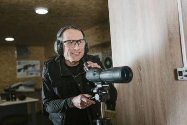 smiling man with binoculars in shooting range