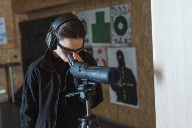 woman looking through binoculars in shooting range