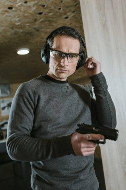 handsome man with gun in shooting range