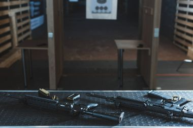 rifles with bullets on table in shooting range