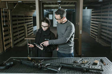 instructor showing pistol to customer in shooting range