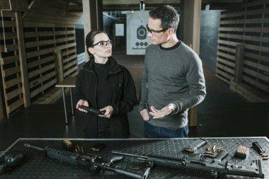 instructor describing gun to female client in shooting range