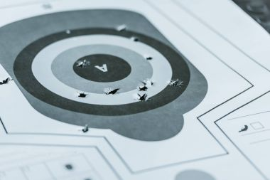 used gun target with holes after bullets in shooting range