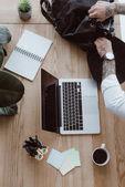 Schnappschuss von Geschäftsmann beim Öffnen des Rucksacks während der Arbeit mit Laptop am Arbeitsplatz