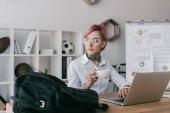 Fotografie mladá podnikatelka držící šálek kávy a koukal při používání notebooku na pracovišti