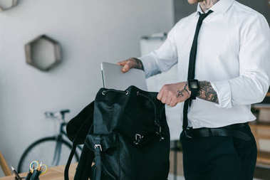 cropped shot of young tattooed businessman putting laptop into backpack