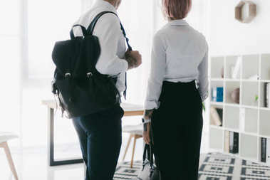 cropped shot of young couple in formal wear leaving office together