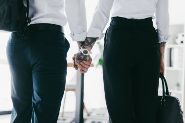 cropped shot of couple in formal wear holding hands in office