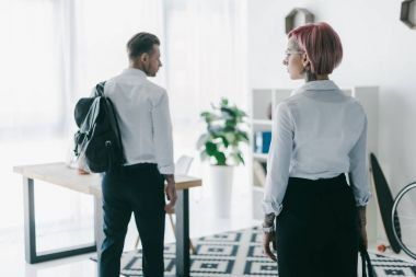 back view of young businesswoman looking at handsome businessman with backpack leaving office