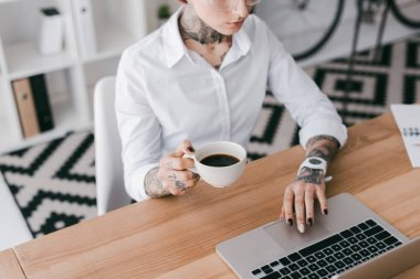 Cropped shot of young businesswoman with tattoos holding cup of coffee and using laptop stock vector