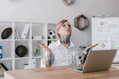 frowned young businesswoman in eyeglasses looking up while sitting at workplace
