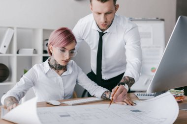 young tattooed colleagues in formal wear working with blueprint in office