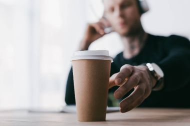 close-up view of young businessman reaching for paper cup on table