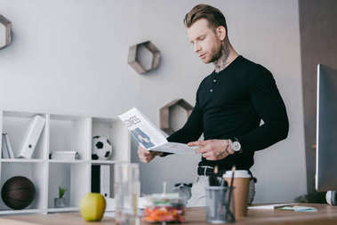 handsome young tattooed businessman reading newspaper in office