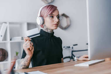 young tattooed businesswoman in headphones holding credit card and using desktop computer