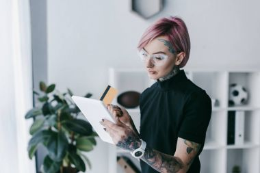 young tattooed businesswoman in eyeglasses holding credit card and using