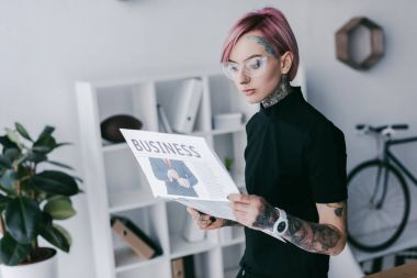 young tattooed businesswoman in eyeglasses reading newspaper at workplace
