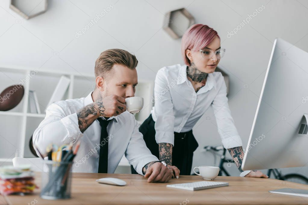 young tattooed business people using desktop computer together