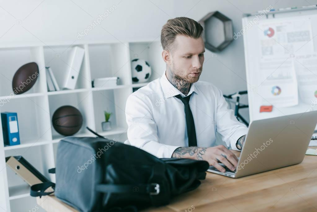 handsome young tattooed businessman using laptop in office