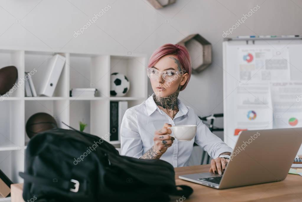 young businesswoman holding cup of coffee and looking away while using laptop at workplace