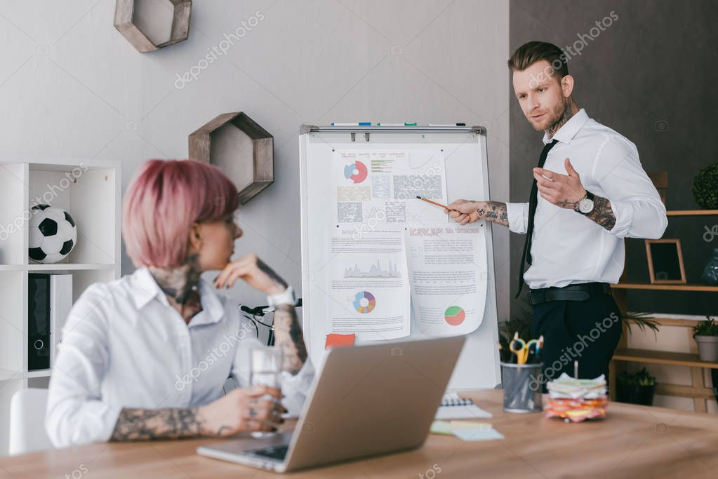young businesswoman using laptop and looking at male colleague pointing at whiteboard  with charts