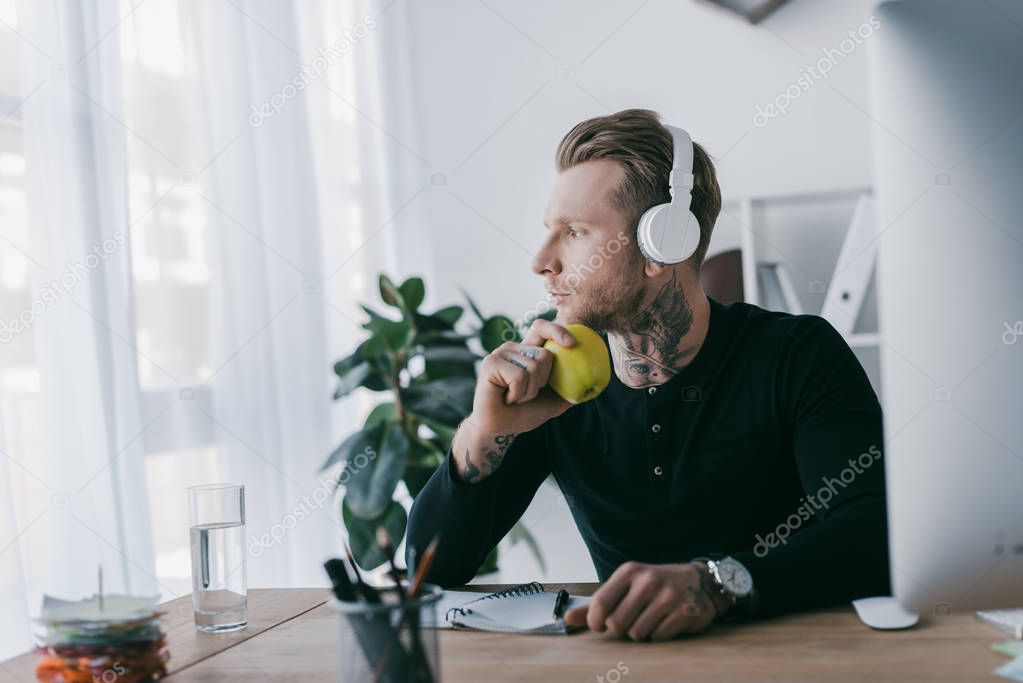 pensive young businessman in headphones holding apple and looking away at workplace