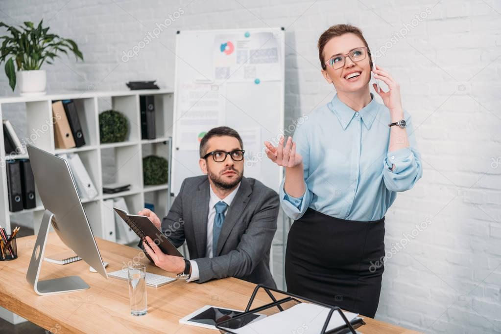 businessman trying to work while his colleague talking by phone and annoying him
