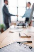 Close-up shot obchodní smlouvy, ležící na stole a rozmazané obchodních partnerů potřesení rukou na pozadí