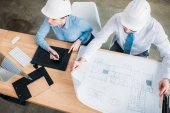 high angle view of architects working with building plan and drawing tablet at office