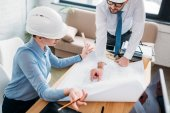 high angle view of architects working with building plan at office