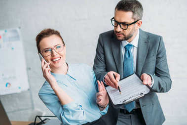 businessman asking his colleague to sign document while she talking by phone and annoying him