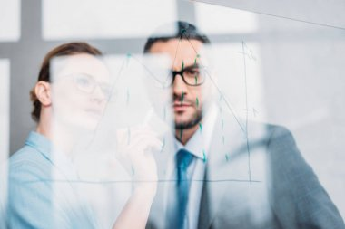 confident businesspeople drawing graphs on glass presentation board