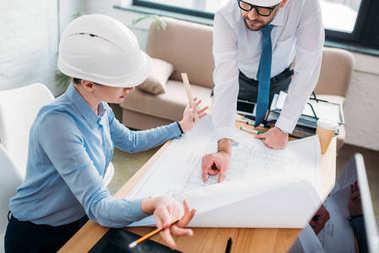 High angle view of architects working with building plan at office stock vector
