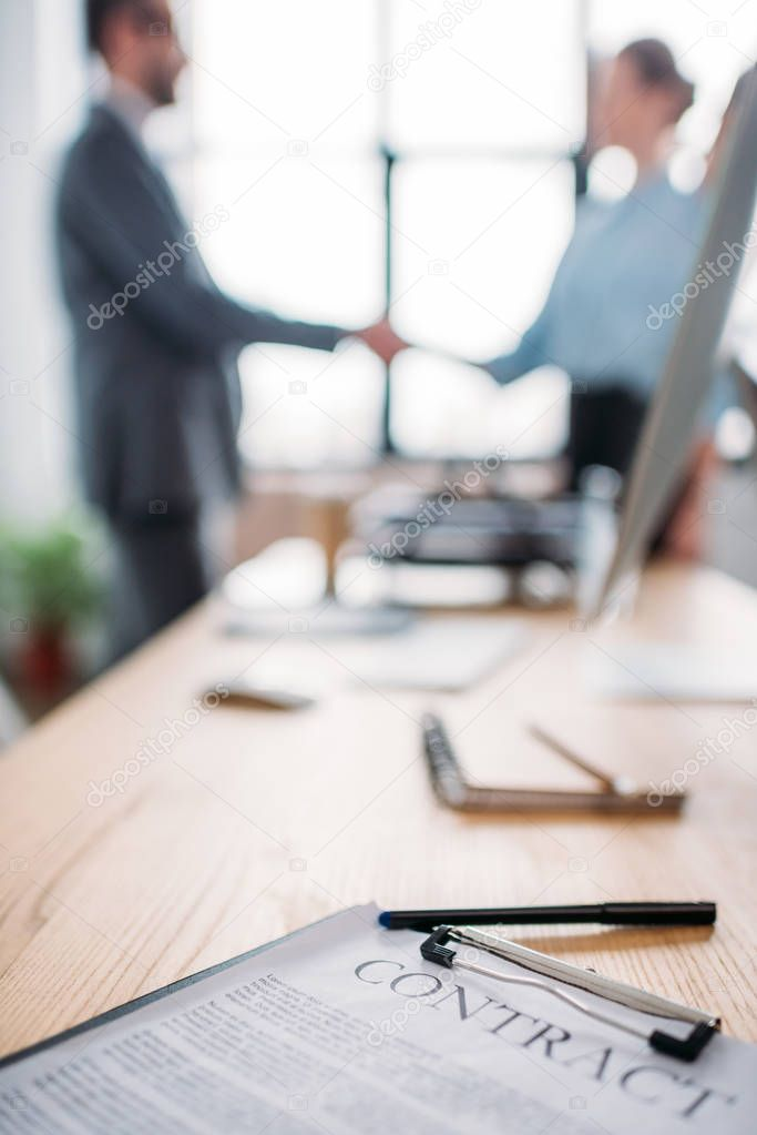 close-up shot of business contract lying on table and blurred business partners shaking hands on background