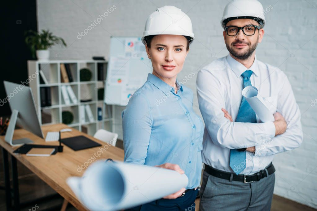 smiling architects standing at modern office with building plans