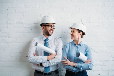 Architects in hard hats standing in front of white brick wall with blueprints stock vector