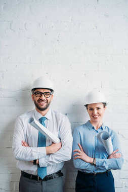 smiling architects in hard hats standing in front of white brick wall with blueprints