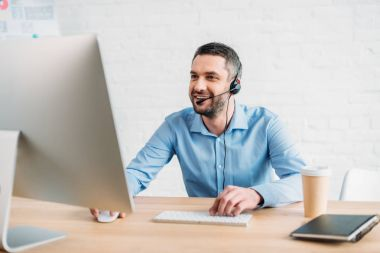 Handsome adult call center worker working with computer at office stock vector