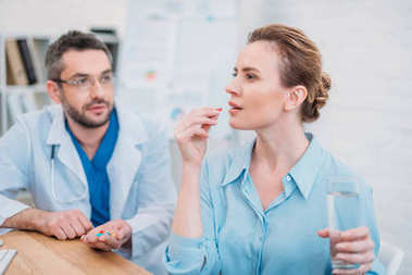 businesswoman taking pill while doctor giving consultation