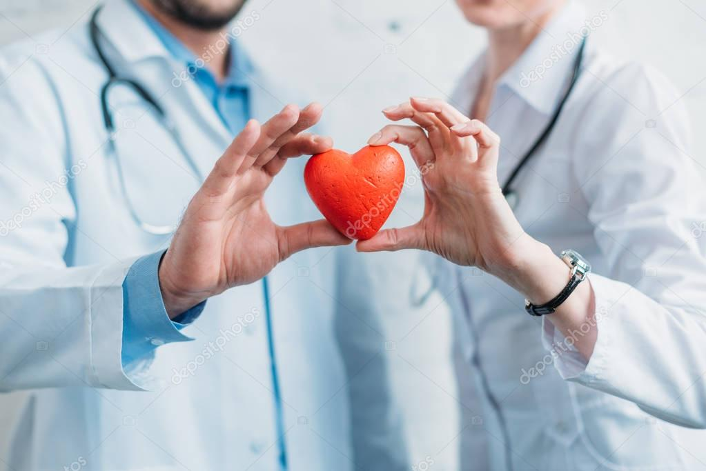 cropped shot of doctors holding toy heart together
