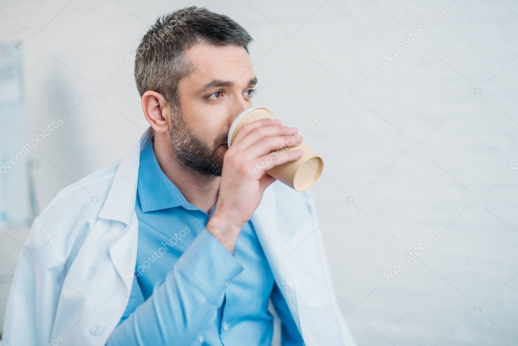 exhausted doctor drinking coffee from paper cup and looking away