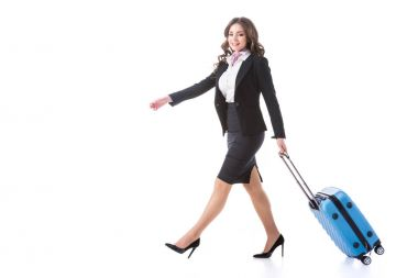 attractive stewardess walking with bag on wheels isolated on white
