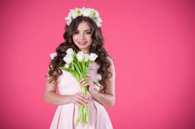 beautiful girl with flowers wreath on head and bouquet of tulips looking at camera isolated on pink